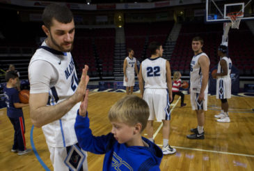 BANGOR, MAINE -- 10/25/2016 - University of Maine's Ilker Er (left) gives a young fan a high five during the basketball media day and kids clinic on Tuesday at the Cross Insurance Center in Bangor.  Ashley L. Conti | BDN